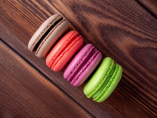 Вкусное сладкое миндальное печенье разных цветов на коричневом деревянном фоне. вид сверху, плоская планировка