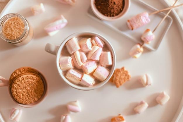 白いテーブルの上のマグカップにマシュマロのお菓子とおいしい甘い芳香のココアドリンクまたはホットチョコレート