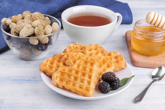 푸른 나무 테이블에 꿀과 차를 넣은 하트 모양의 맛있는 달콤한 벨기에 와플. 아침밥.