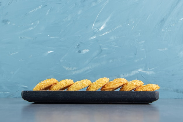 Delicious sweet biscuits on black plate.