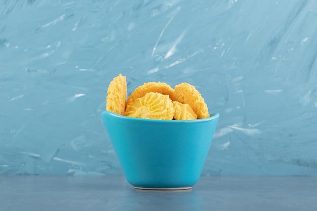 青いボウルにおいしい甘いビスケット。
