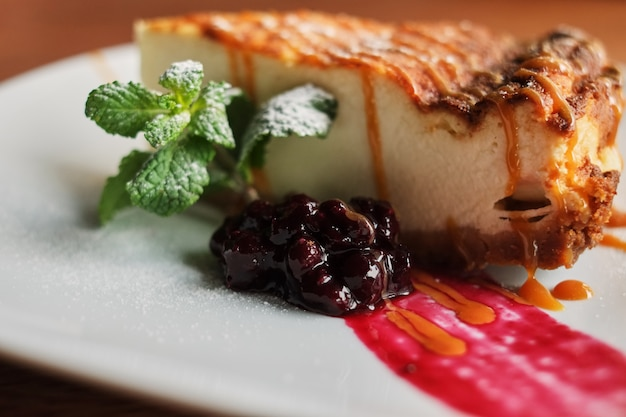 Delicious and sweet blueberry cheesecake on white plate served with whipped cream