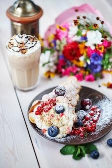 Вкусные сладкие пузырьковые вафли с ягодами на деревянном столе