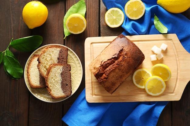 Вкусный сладкий торт с лимонами на деревянном столе, вид сверху