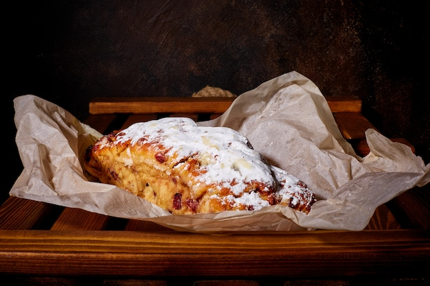 A delicious sweet cake sprinkled with powdered sugar lies on waxed paper and a wooden tray