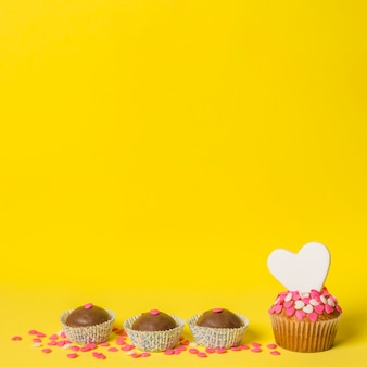 Delicious sweet candies and cake with decorative heart