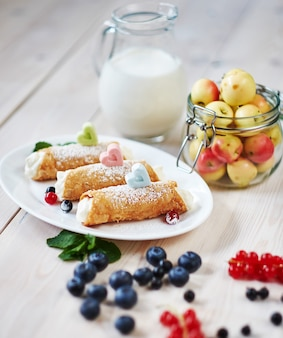Delicious sweet cannoli with berry on a wooden table.