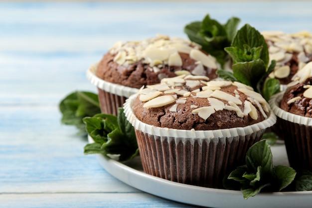 Вкусные сладкие шоколадные кексы с миндальными лепестками и мятой на синем деревянном столе. Premium Фотографии