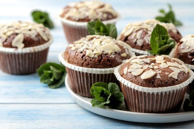 Вкусные сладкие шоколадные кексы с миндальными лепестками и мятой на синем деревянном столе.