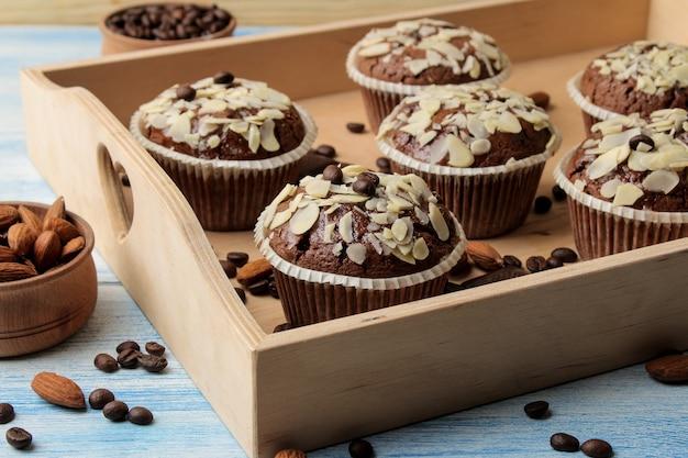 Вкусные сладкие шоколадные кексы с миндальными лепестками на деревянном подносе рядом с кофейными зернами на синем деревянном столе.