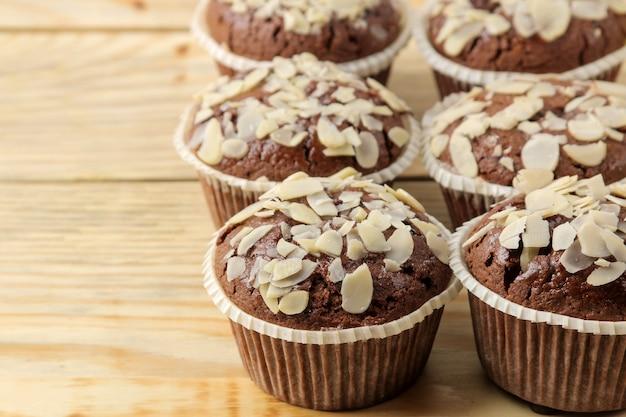 Вкусные сладкие шоколадные кексы с миндальными лепестками рядом с миндальными орехами на натуральном деревянном столе. крупный план