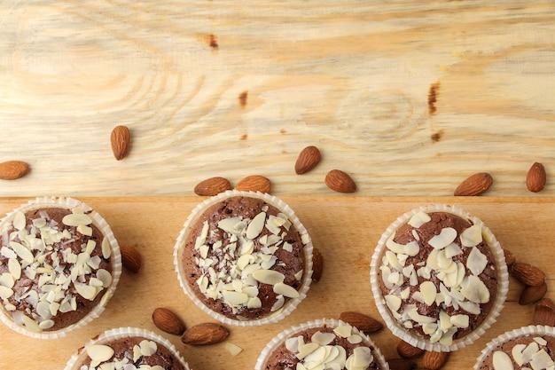 Вкусные сладкие шоколадные кексы с миндальными лепестками рядом с миндальными орехами на натуральном деревянном столе. вид сверху