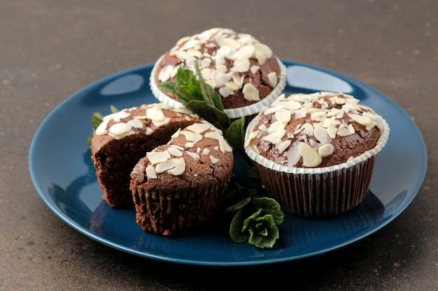 Вкусные сладкие шоколадные кексы с миндальными лепестками рядом с мятой и миндалем в тарелке на темном столе.