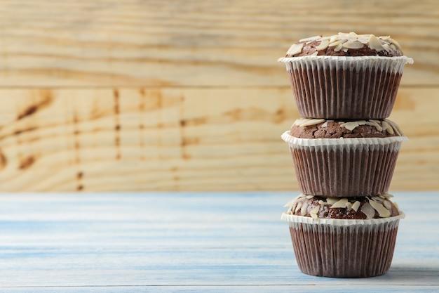Вкусные сладкие шоколадные кексы с миндальными лепестками на синем деревянном столе.