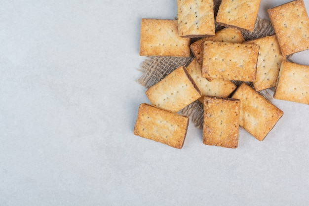 Delicious sweet crackers on sackcloth on white background. high quality photo