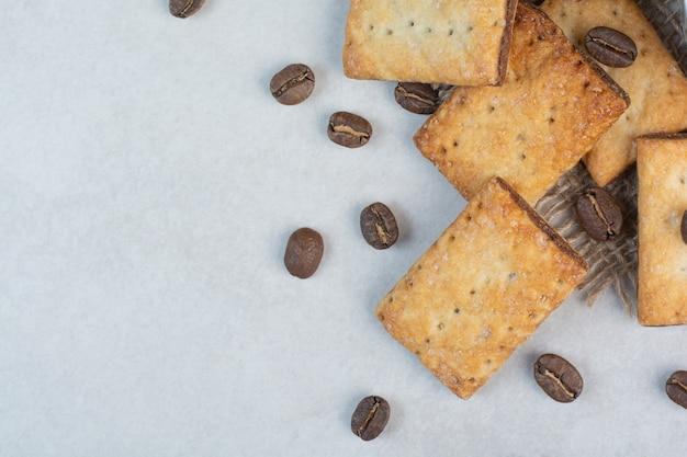 Deliziosi cracker dolci con chicchi di caffè su tela di sacco. foto di alta qualità