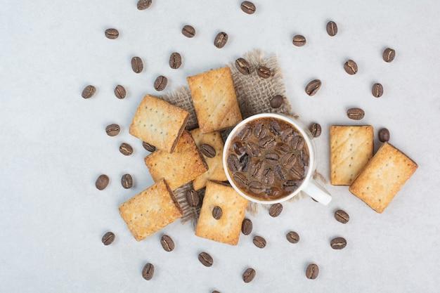 Вкусные сладкие крекеры с белой чашкой кофе на вретище. фото высокого качества