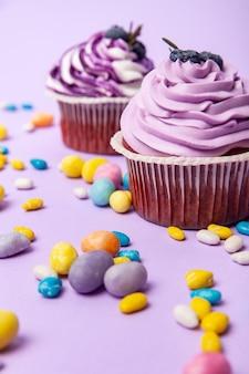 ライラックの背景に散らばったカラフルなキャンディーの間に配置されたブルーベリーのフロスティングとベリーのおいしい甘いカップケーキ