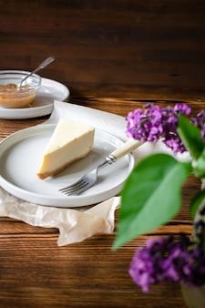 木製の素朴な背景においしい甘いデザートクラシックチーズケーキニューヨークスライス。セラミックプレート上のおいしいケーキのスライスは、デザートフォークとリンゴジャムとライラックの花を添えて。