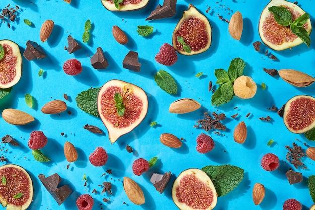 Вкусный сладкий десертный узор из спелого инжира, орехов, шоколада, свежей малины, листьев малины на синем фоне - натуральных ингредиентов для энергии здорового питания. вид сверху.