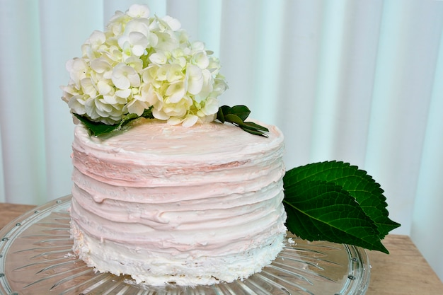 Delicious sweet dessert rustic naked cake with white flowers on topping