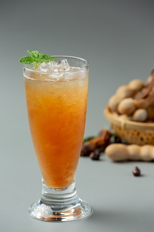 Delicious sweet drink tamarind juice on gray surface
