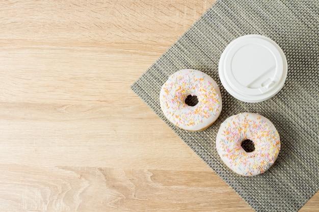 Вкусные, сладкие, свежие пончики и бумажный стаканчик с кофе или чаем на деревянном фоне. концепция завтрак, фаст-фуд, кафе, пекарня.