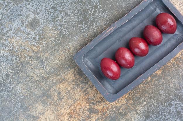 Вкусные сладкие фрукты в темной доске на мраморном фоне. фото высокого качества