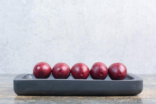Вкусные сладкие фрукты в темной доске на мраморном фоне