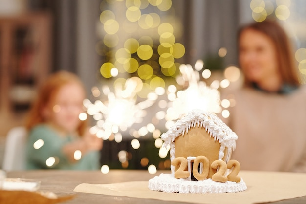Delicious and sweet gingerbread house decorated with whipped cream standing