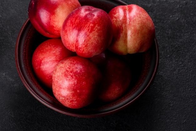 おいしい甘い桃や暗いコンクリート背景に茶色のボウルにネクタリン