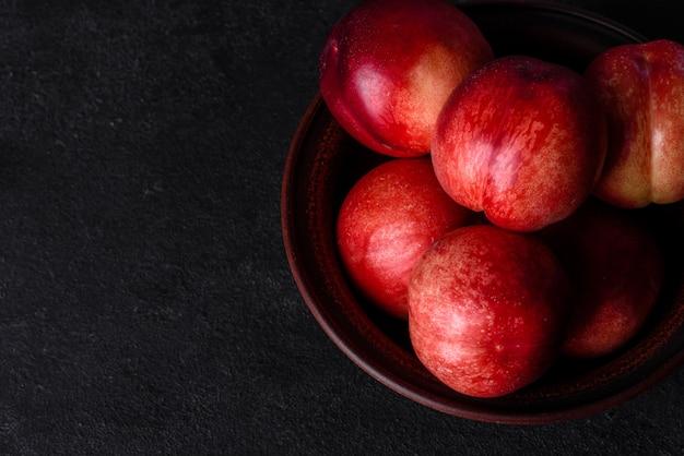 茶色のボウルに美味しい甘い桃やネクタリン