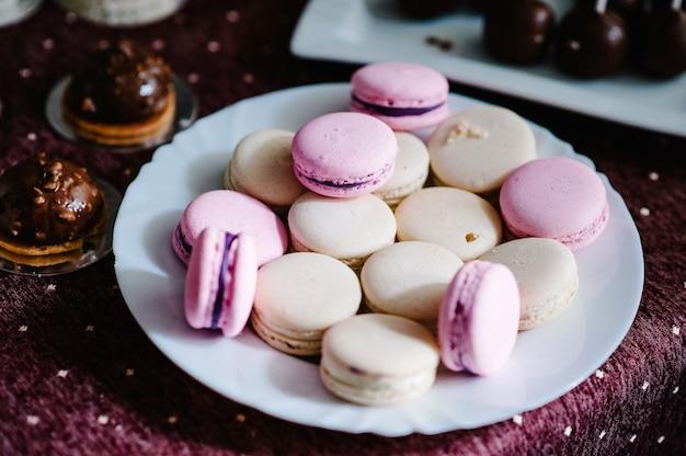 Вкусные сладкие розовые, фиолетовые, пастельные, бежевые макаруны в тарелке
