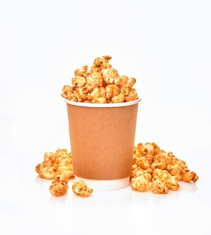 Delicious sweet popcorn with caramel in simple paper cup, isolated on white table.