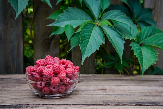 Вкусные сладкие ягоды малины в стеклянной миске на деревянной деревенской поверхности с копией пространства