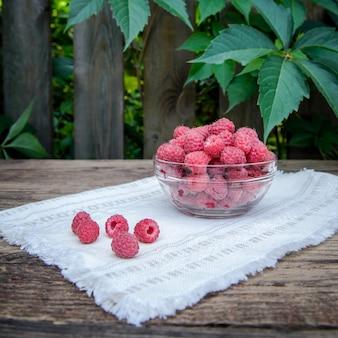 Вкусные сладкие ягоды малины в стеклянной миске на деревянной деревенской поверхности