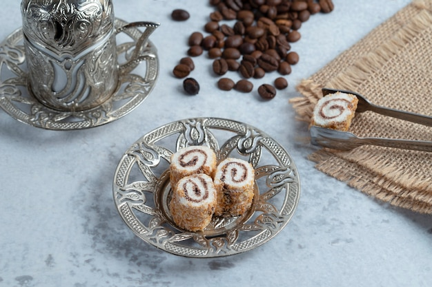 Delicious sweet rolls, coffee beans and turkish coffee on stone background. high quality photo