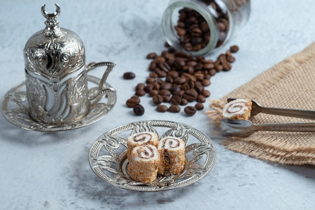 Delicious sweet rolls, coffee beans and turkish coffee on stone.
