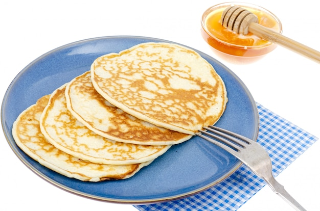Delicious sweet thin pancakes on blue plate.