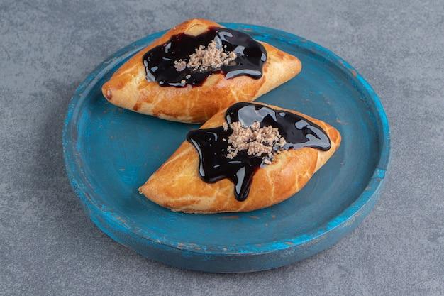 나무 파란색 접시에 맛있는 달콤한 삼각형 과자