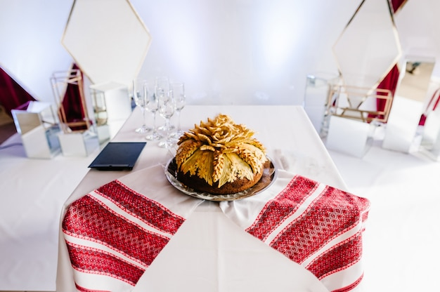 A delicious sweet wedding loaf in the ukrainian style on embroidered towels. festive sweet table.
