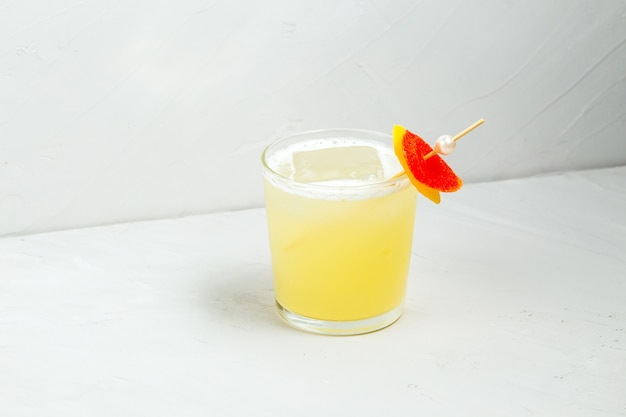 Delicious sweet yellow sour cocktail in a glass