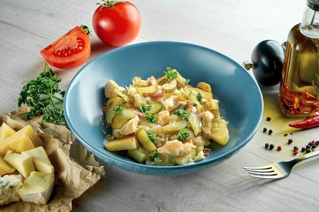 おいしいスイス料理-チーズ、ベーコン、チキン、ポテト、マッシュルームを添えたラクレットを、木製のテーブルの上の青いボウルでお召し上がりいただけます。レストランの食べ物