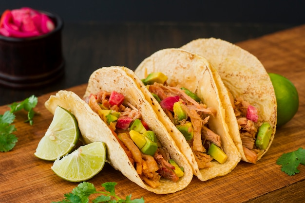 Delicious tacos on wooden board