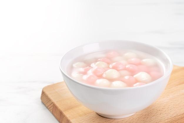 小さなボウルにおいしい湯円、赤と白のご飯餃子ボール。中国の冬至祭のためのアジアの伝統的なお祭り料理、クローズアップ。