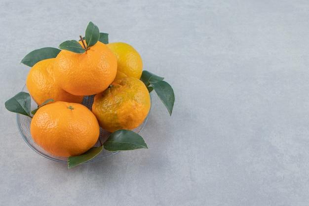 유리 접시에 맛 있는 귤 과일.