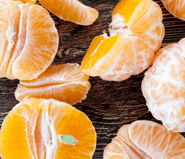 맛있는 감귤, 나무 테이블에 누워 껍질을 벗긴 오렌지 껍질, 비타민이 많은 건강한 감귤류