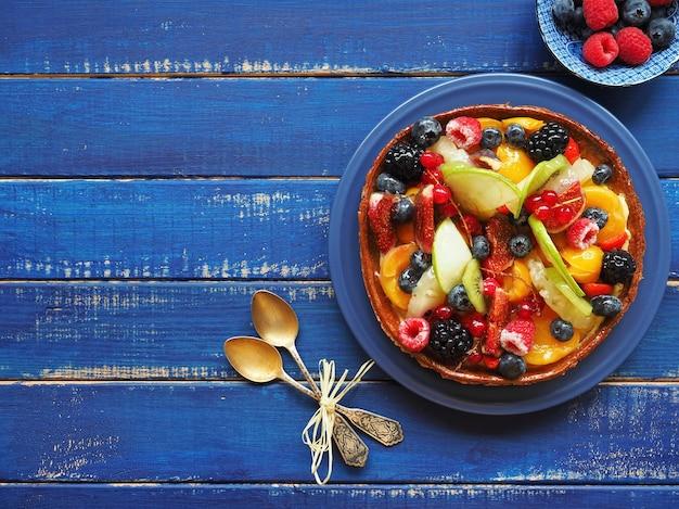 푸른 나무 테이블에 딸기와 이국적인 과일과 함께 맛있는 타트