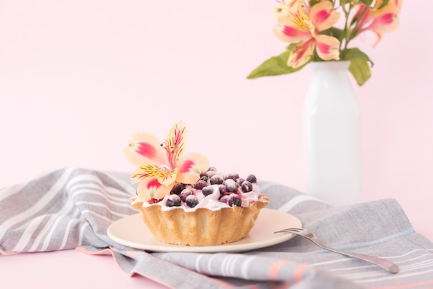 Delicious tart with blueberries and alstroemeria flower on ceramic plate against pink backdrop