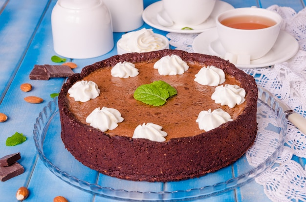 Delicious tart with chocolate cream, cherry, whipped cream and mint leaves on top.